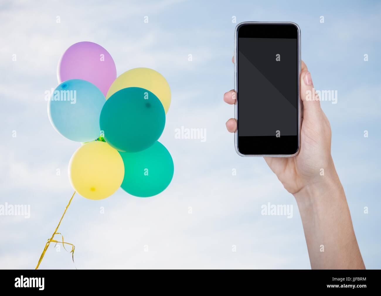 Digital composite of Hand with phone against sunny sky and balloons Stock Photo