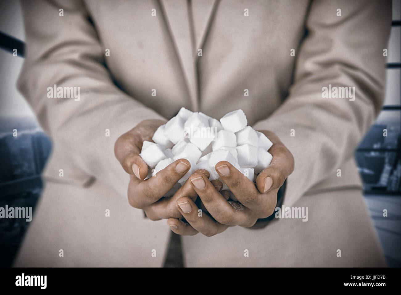 Womans hands cupped with sugar cubes against room with large window showing city - Stock Image