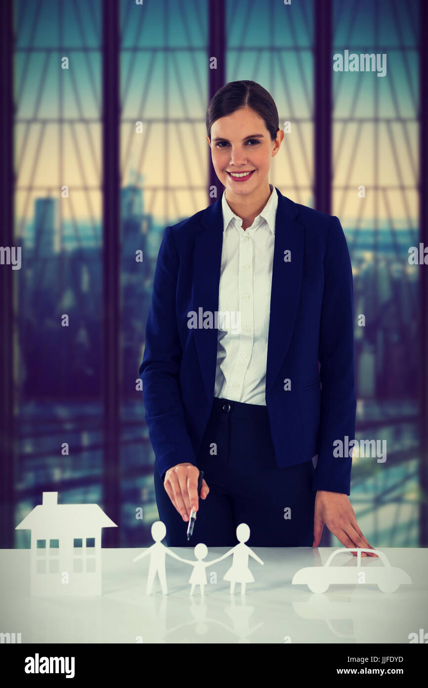 woman drawing a car, a family and a house against room with large window looking on city - Stock Photo