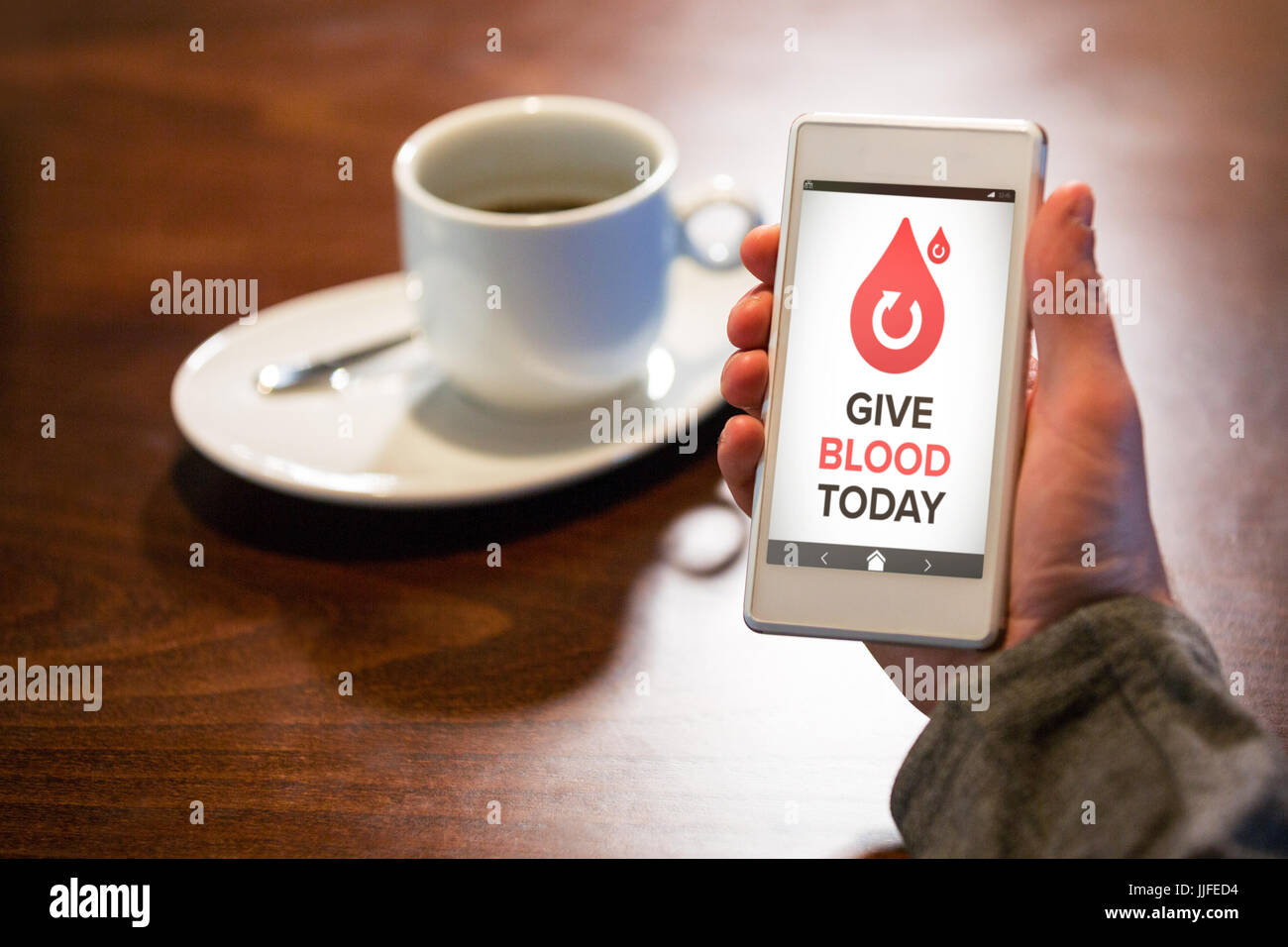Give Blood Today text with icons on screen against hand holding mobile phone - Stock Image
