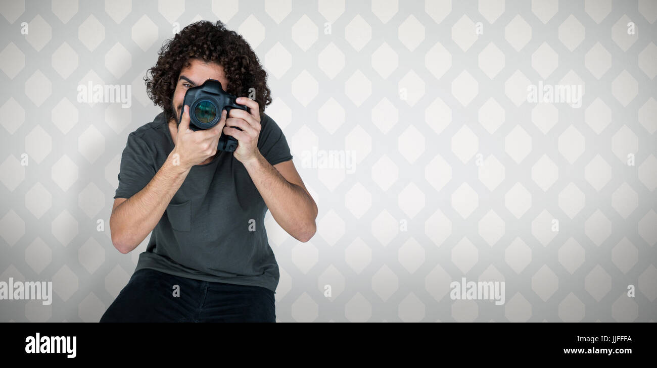 Full length of male photographer taking picture  against room with wooden floor - Stock Image