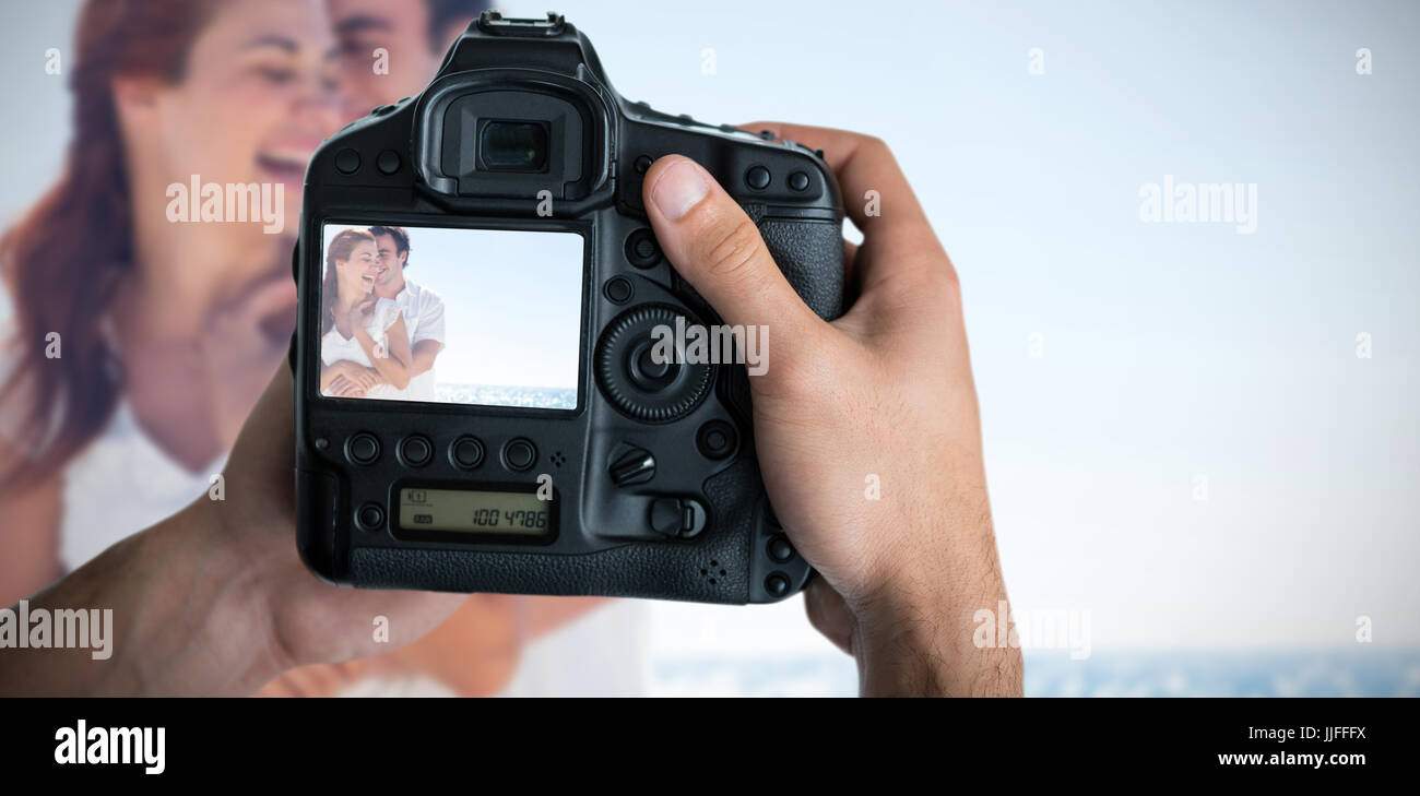 Composite image of cropped image of hands holding camera - Stock Image