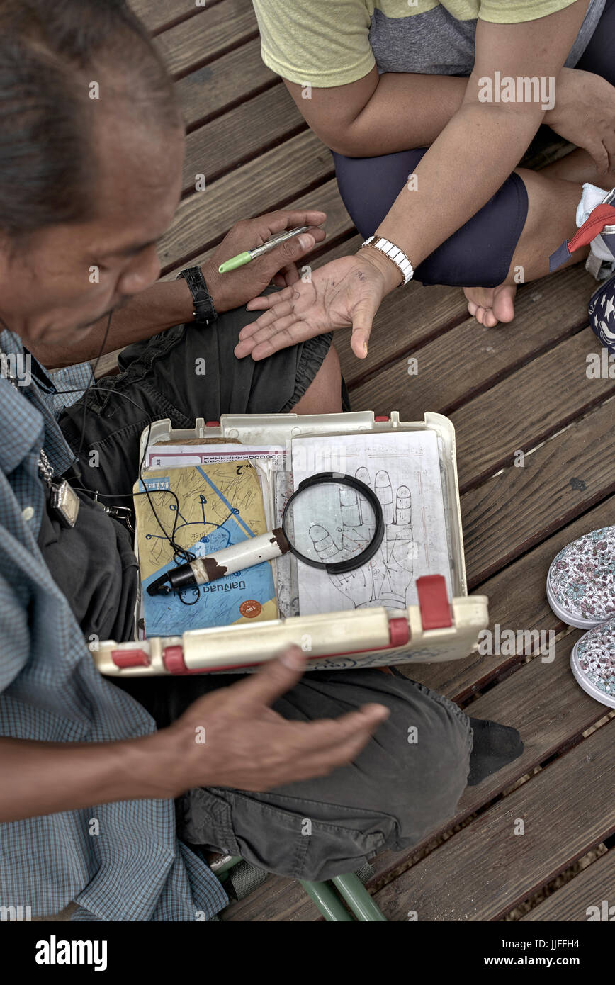Fortune teller and hand palm reader with equipment. Thailand Southeast Asia - Stock Image