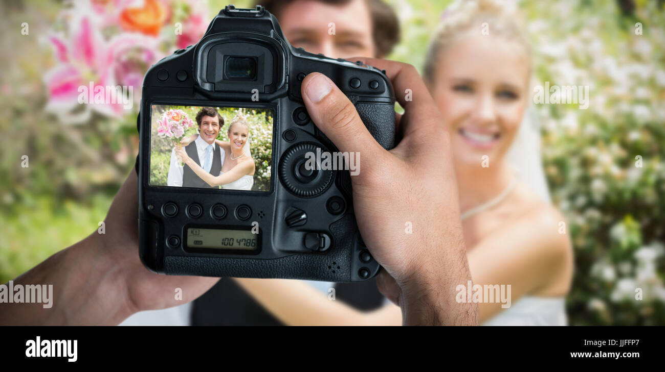 Cropped image of hands holding camera  against portrait of romantic newlywed couple Stock Photo