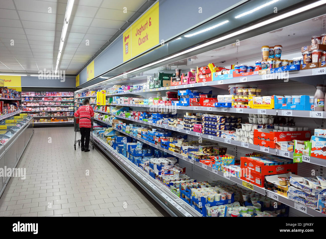 Customers with a trolley shopping in the chilled dairy products of a Netto Marken-Discount supermarket. - Stock Image