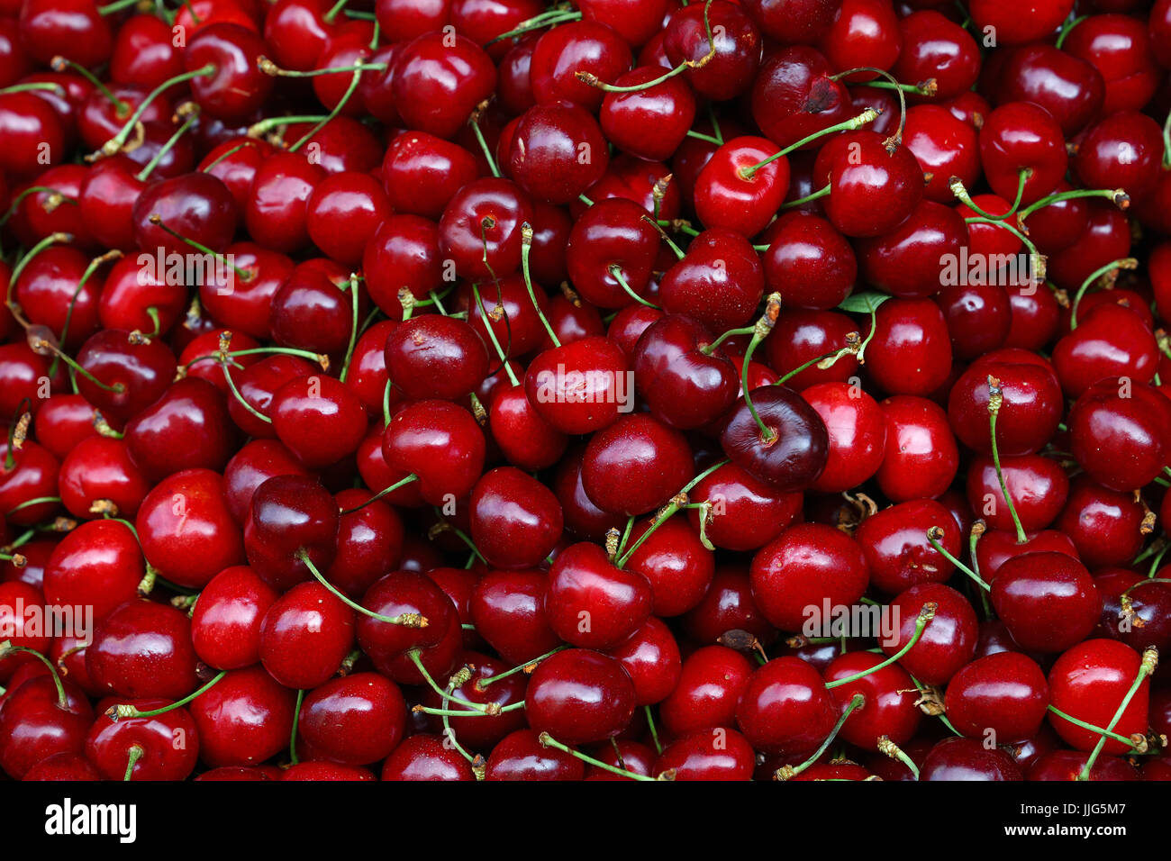 Heap of fresh red ripe sweet black cherry berries on retail market stall display, close up, high angle view - Stock Image