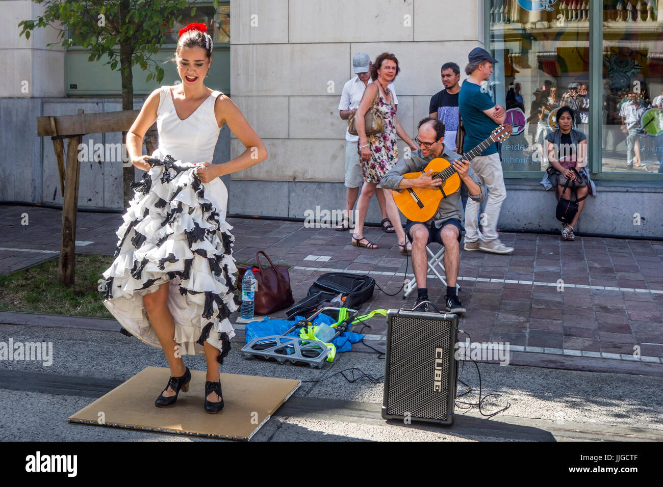 Guitarist and flamenco dancer with traditional white dress dancing as street performance during summer festivities - Stock Image