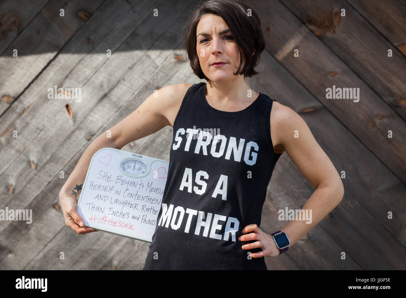 b414ece54d6be Strong woman holding a scale with her hand on her hip in a black tank top