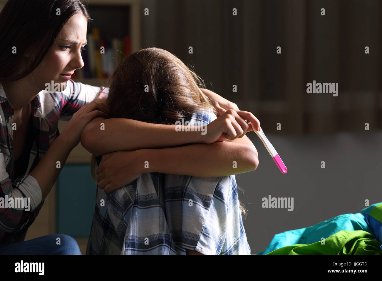 Sister comforting to a pregnant sad teen in her bedroom with a dark light in the background - Stock Image