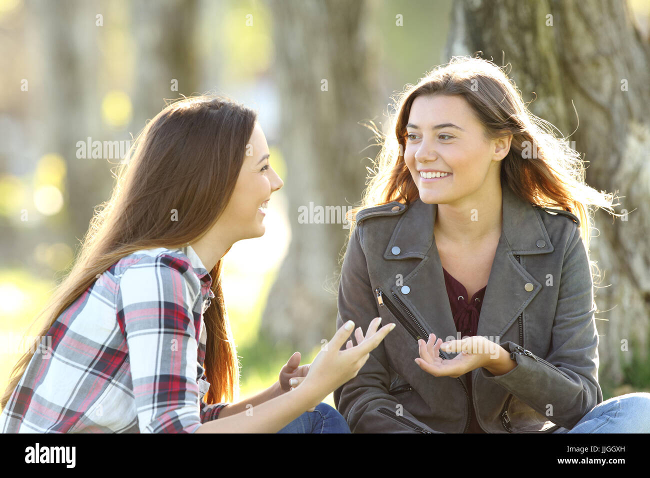 Two friends talking and laughing sitting on the grass in a park - Stock Image