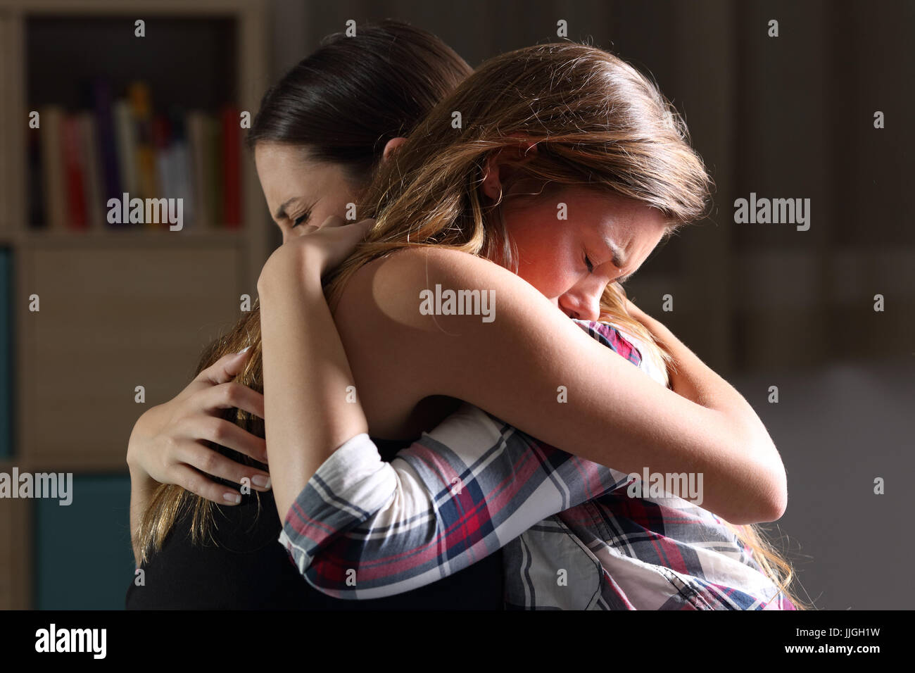 Side view of two sad good friends embracing in a bedroom in a house interior with a dark light in the background - Stock Image