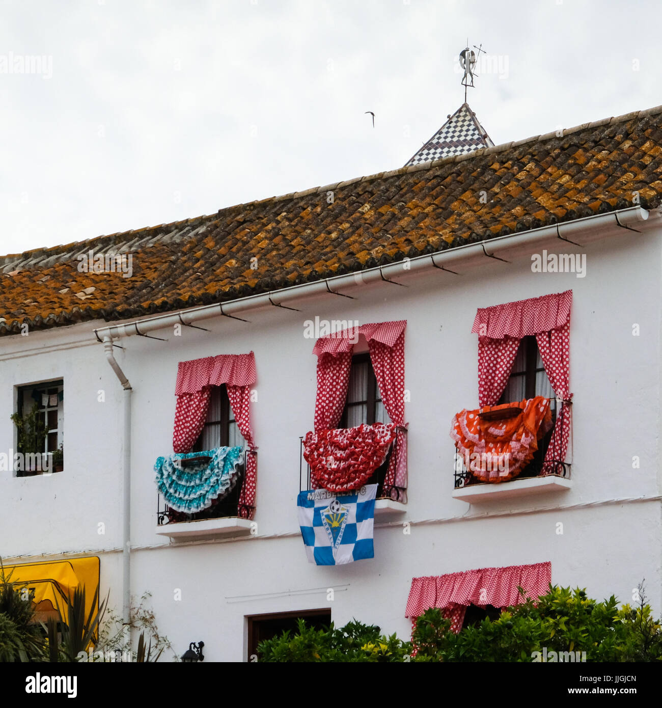Traditional Spanish Dresses adorning Balconies on a Building in Marbella - Stock Image