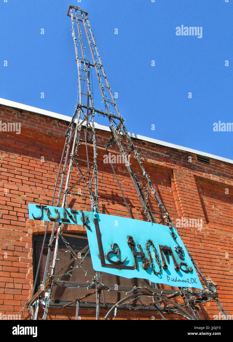 A metal Eiffel Tower look-alike stands with Junklahoma sign at an antique shop in Piedmont Oklahoma. - Stock Image