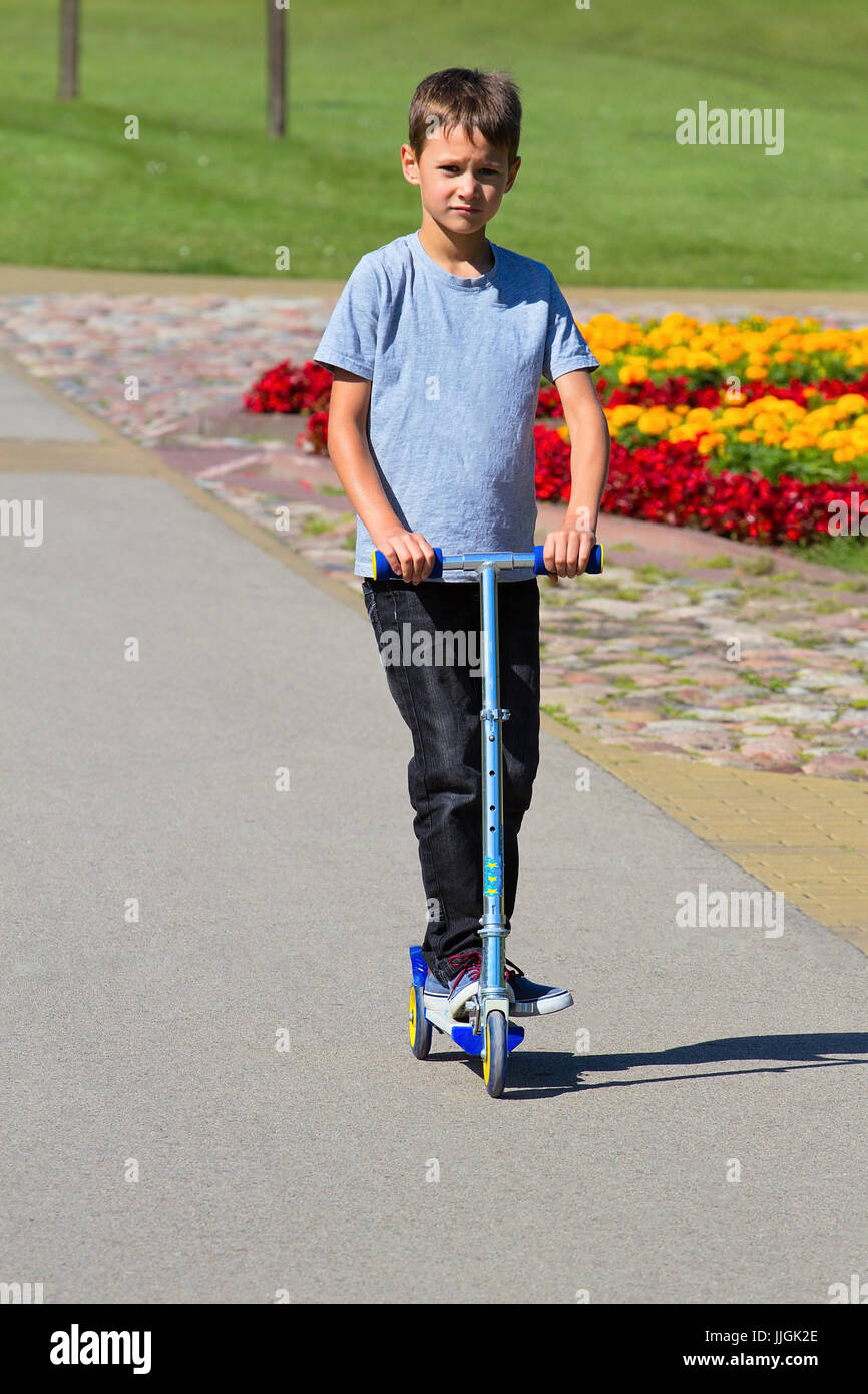 Boy riding in his scooter in the park - Stock Image