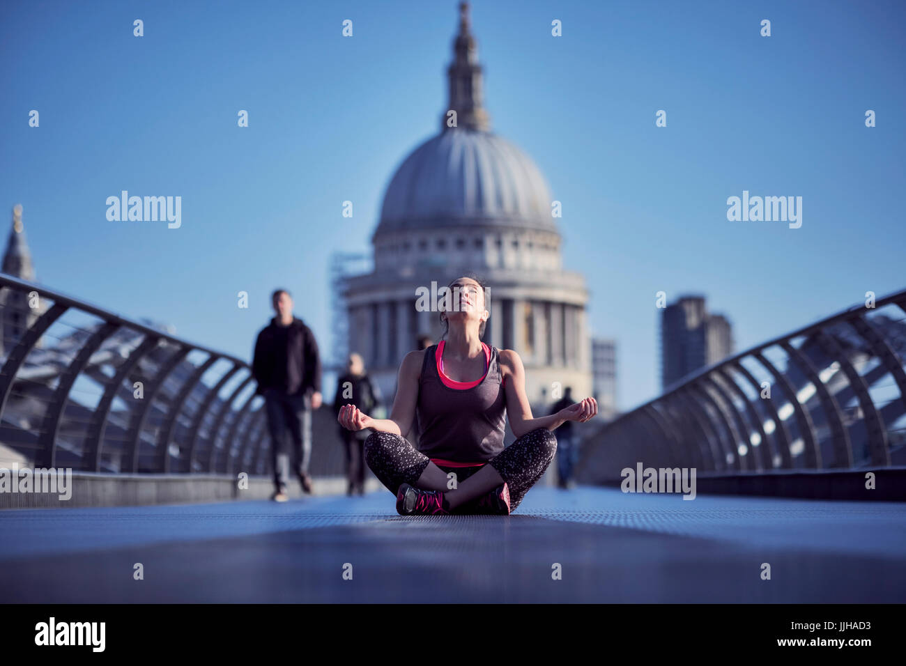 A woman meditating on the Millennium Bridge with St Paul's Cathedral in the background. - Stock Image