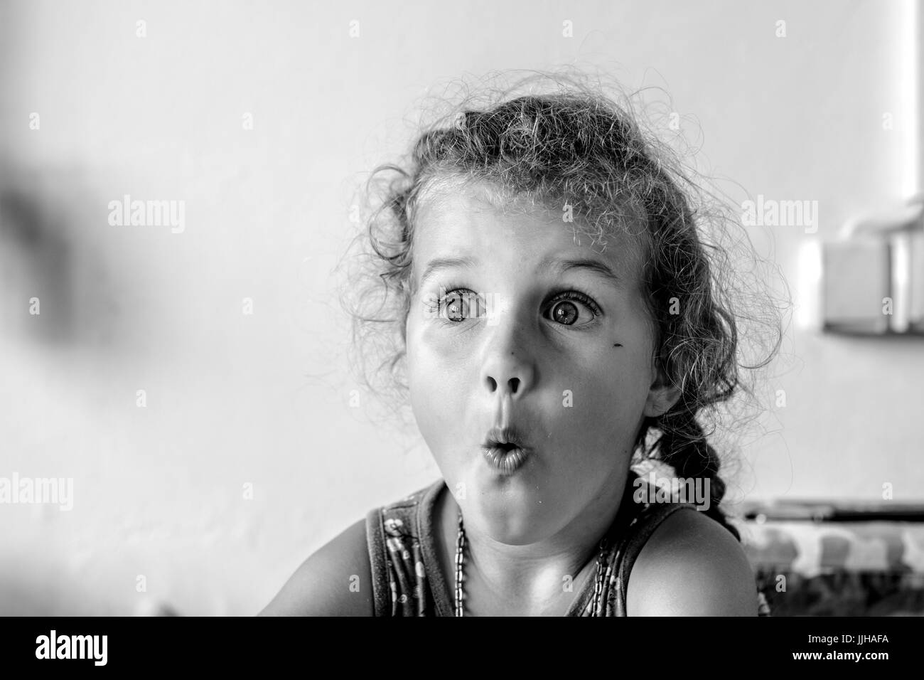 Black and white picture with surprised young girl with curly hair looking to the right - Stock Image