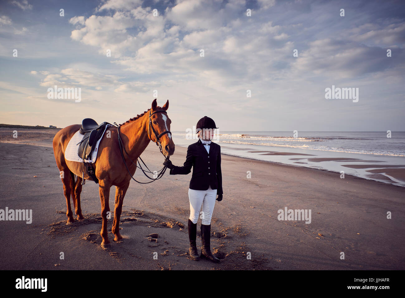 A young woman standing with her horse on the beach. - Stock Image