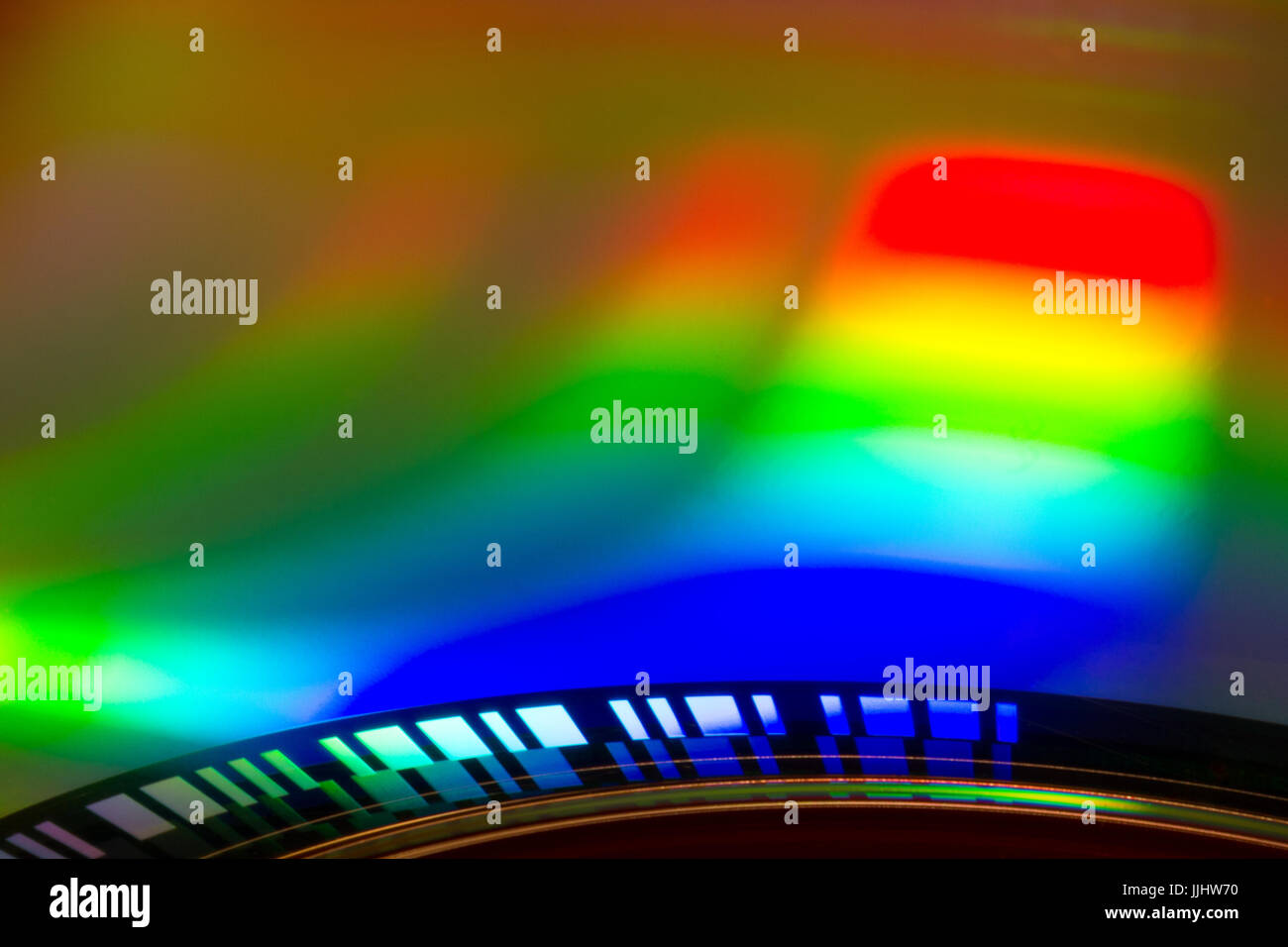 Rainbow colours caused by refracting light on surface of cd. - Stock Image