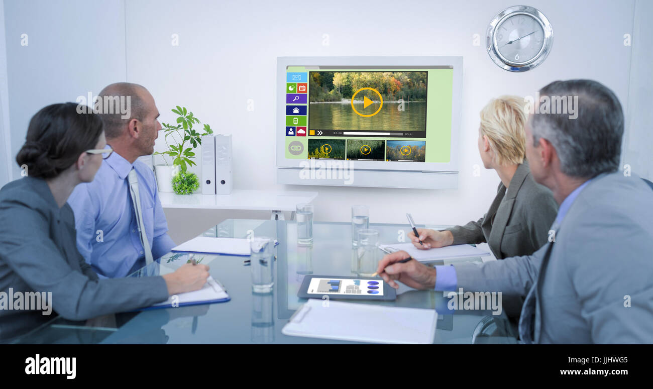 Business team looking at time clock  against digitally generated image of various video and icons displayed Stock Photo
