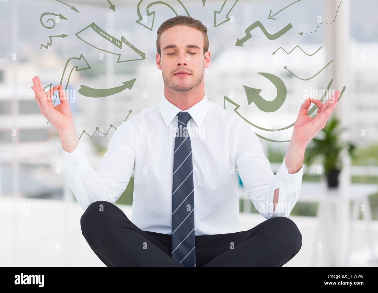 Business man meditating in blurry white office surrounded by 3D green arrow doodles - Stock Image