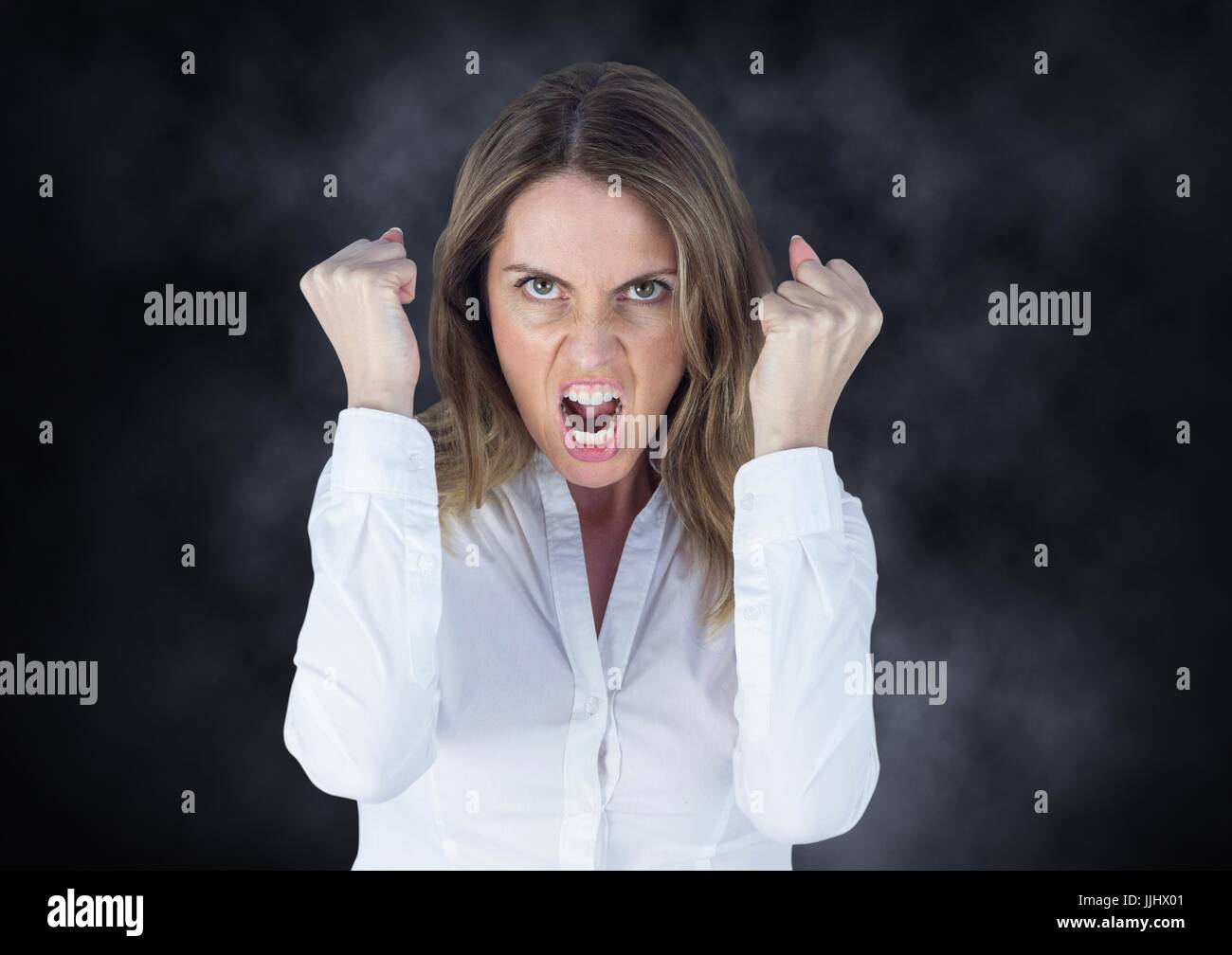 Angry business woman against mist - Stock Image