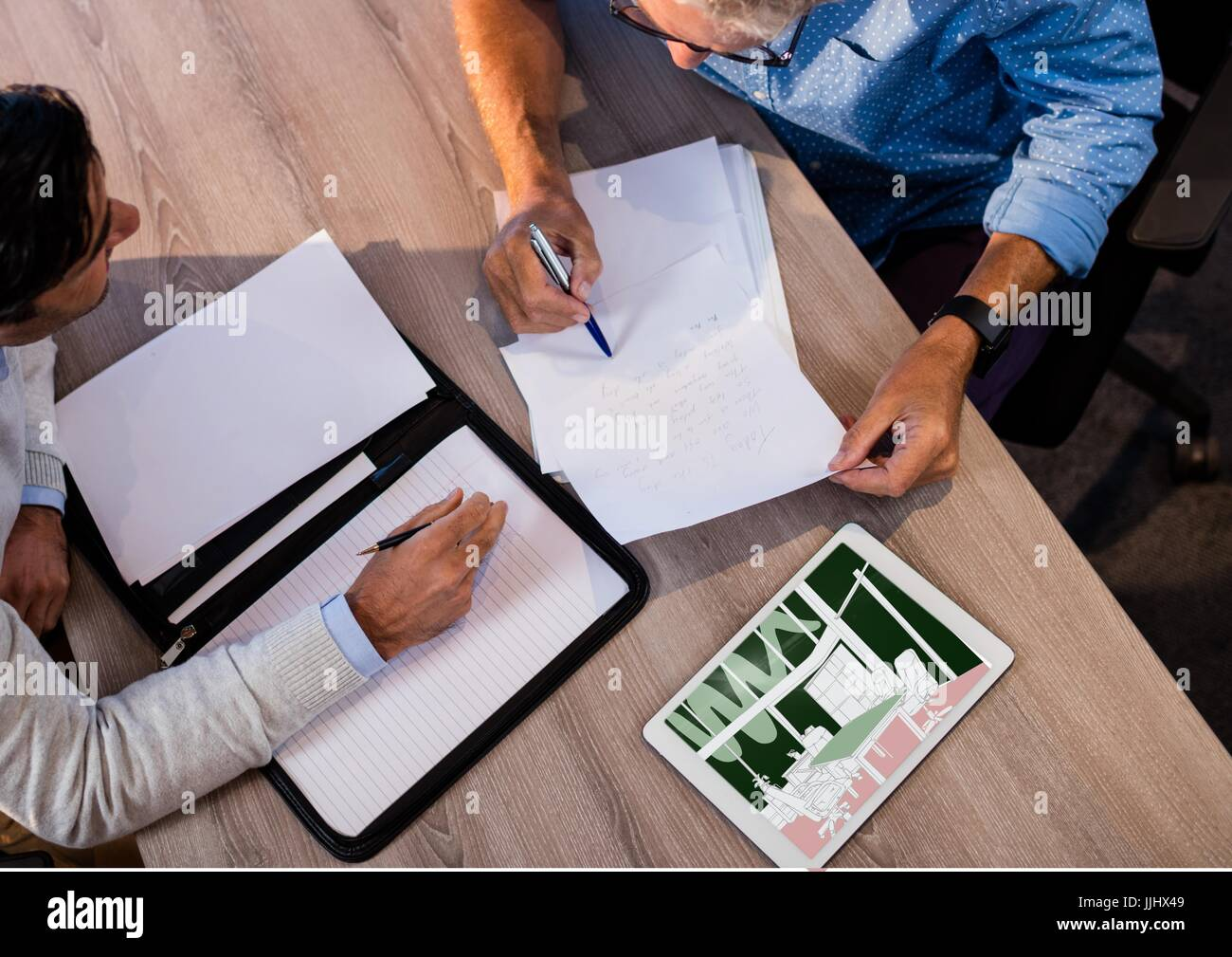 top view of a desk with two businessmen working. Tablet on the desk with new office meeting room blu - Stock Image