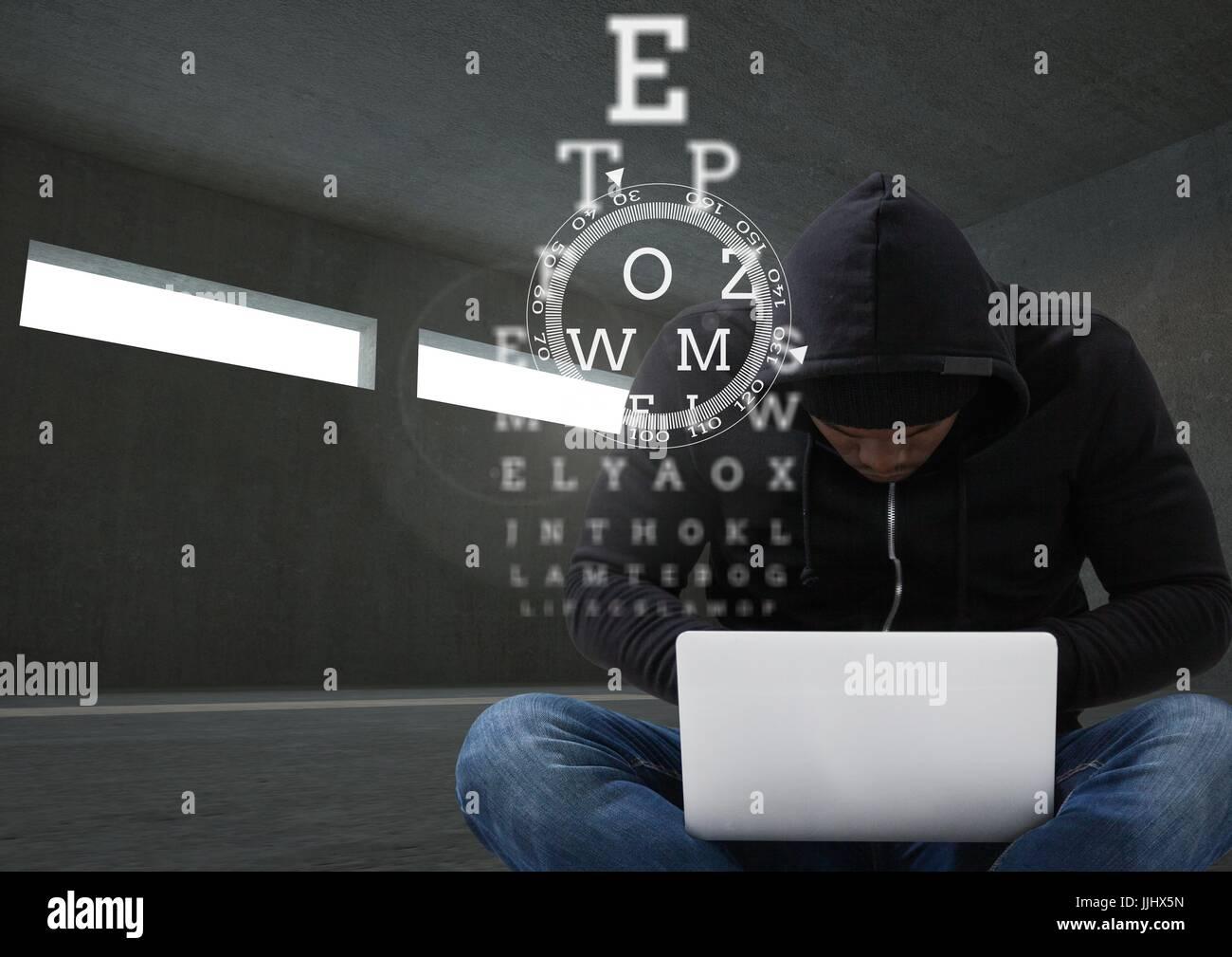 Hacker working on laptop in dark room behind digital scriptures - Stock Image