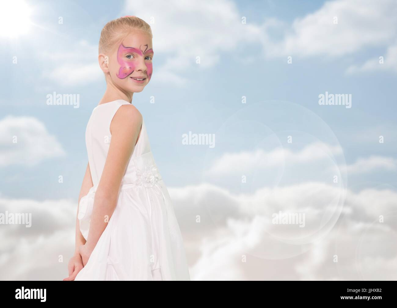 Girl with pink facepaint against sky with flare - Stock Image