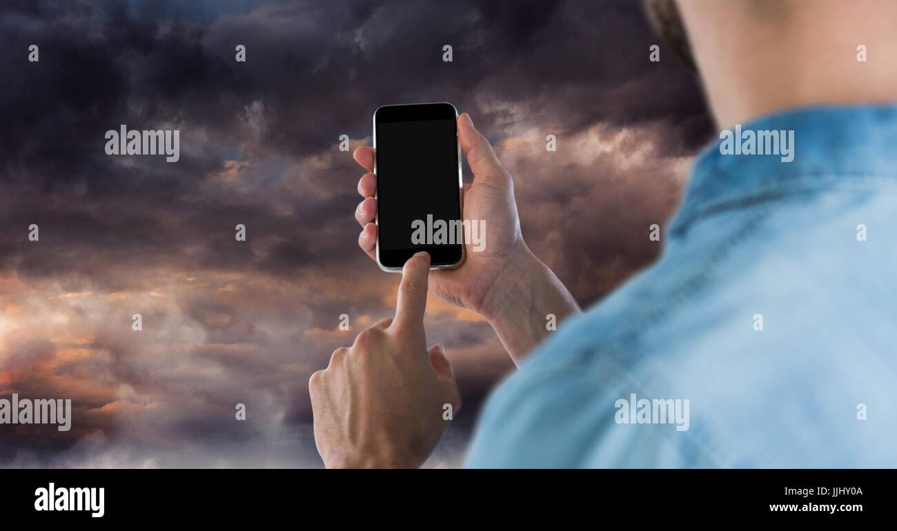 Part of a man using a mobile phone against 3D darkness - Stock Image