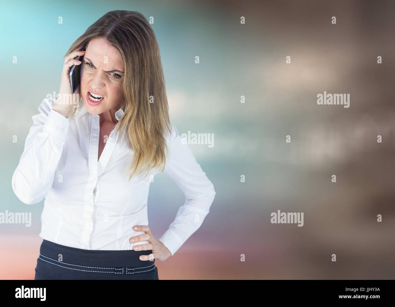Angry business woman on phone against blurry blue brown background - Stock Image