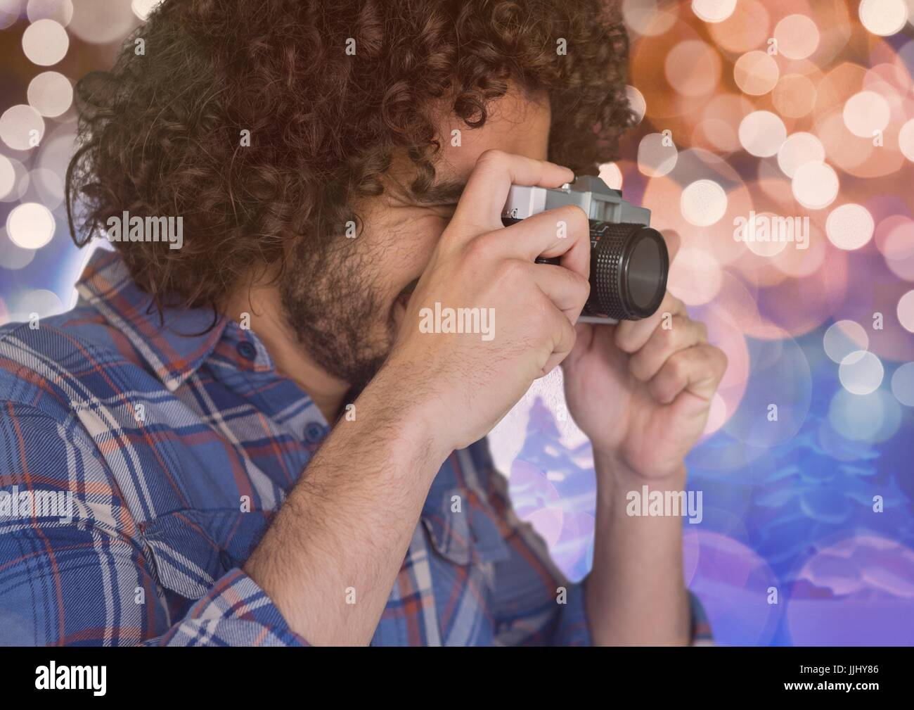 photographer foreground taking a photo with vintage camera. Blurred  blue and orange lights backgrou - Stock Image
