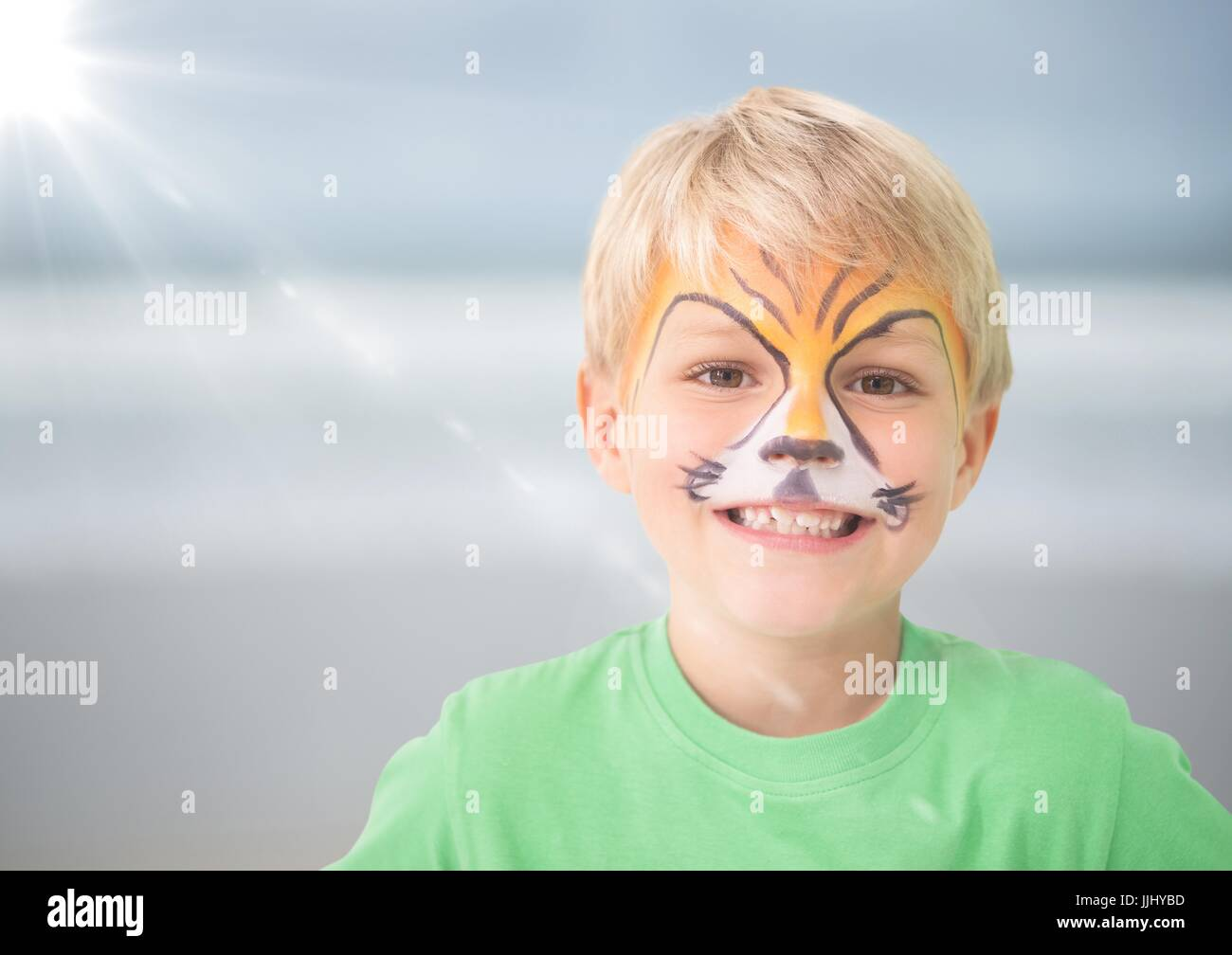 Boy with tiger facepaint against blurry beach with flare - Stock Image