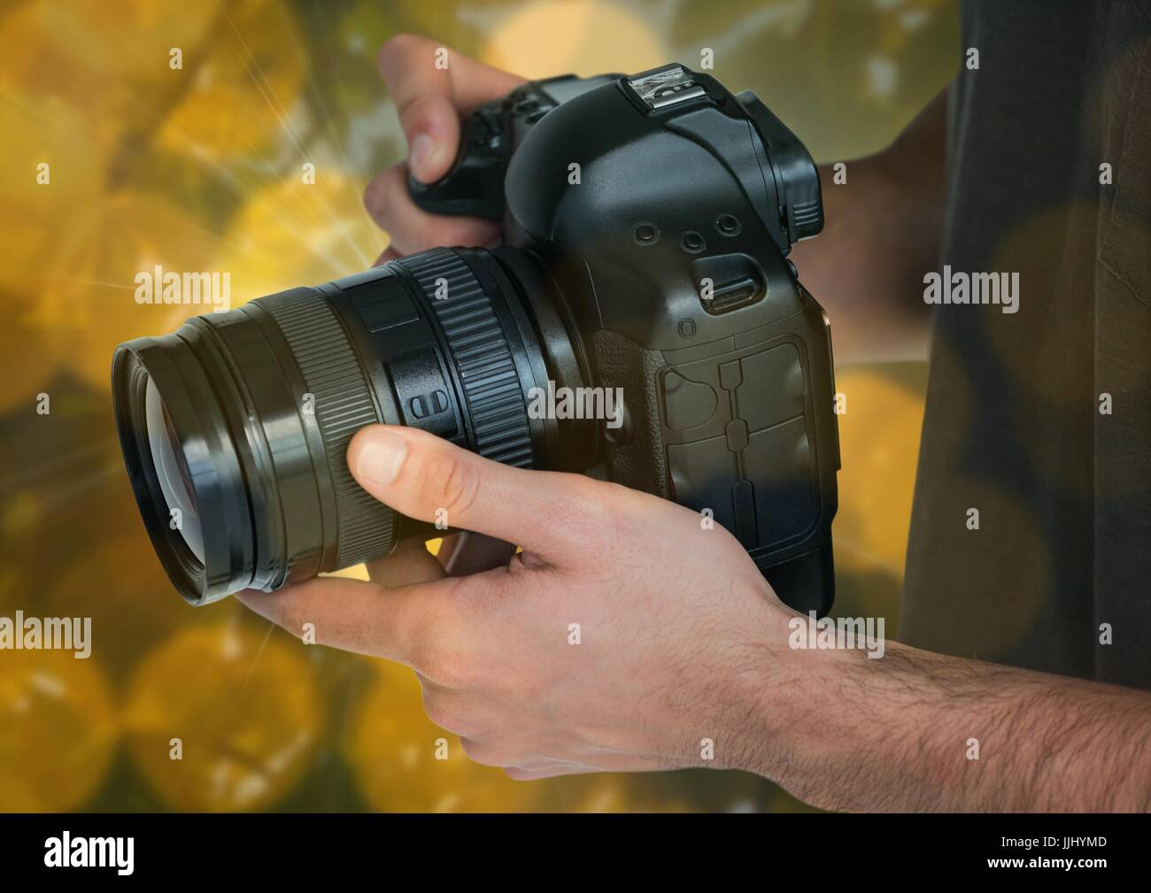 camera on photographer hands. Green and yellow bokeh background and overlap. - Stock Image