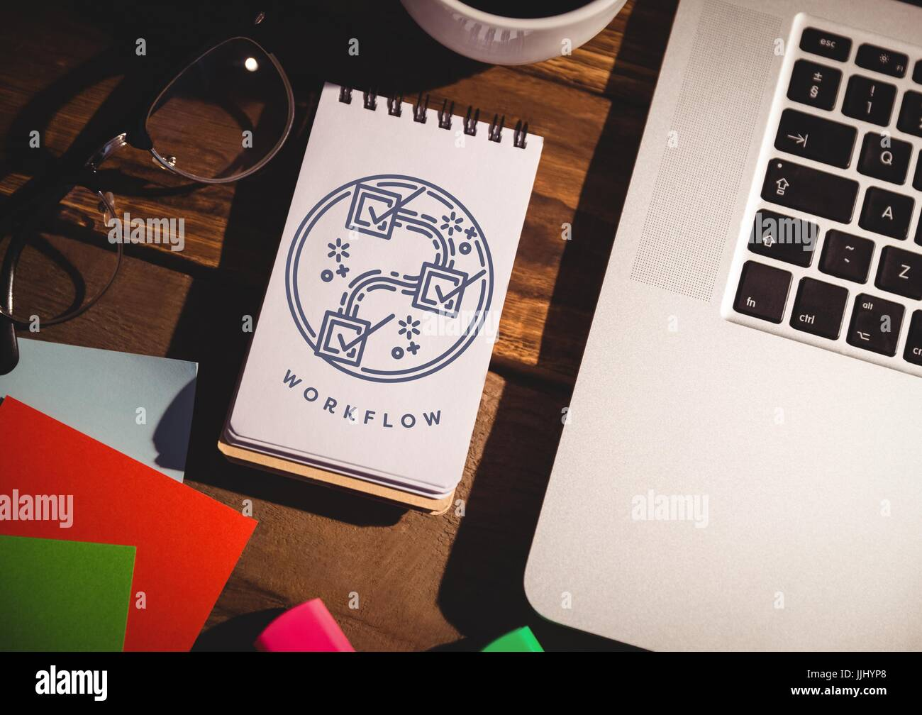 Navy workflow graphic on notepad next to laptop and glasses - Stock Image