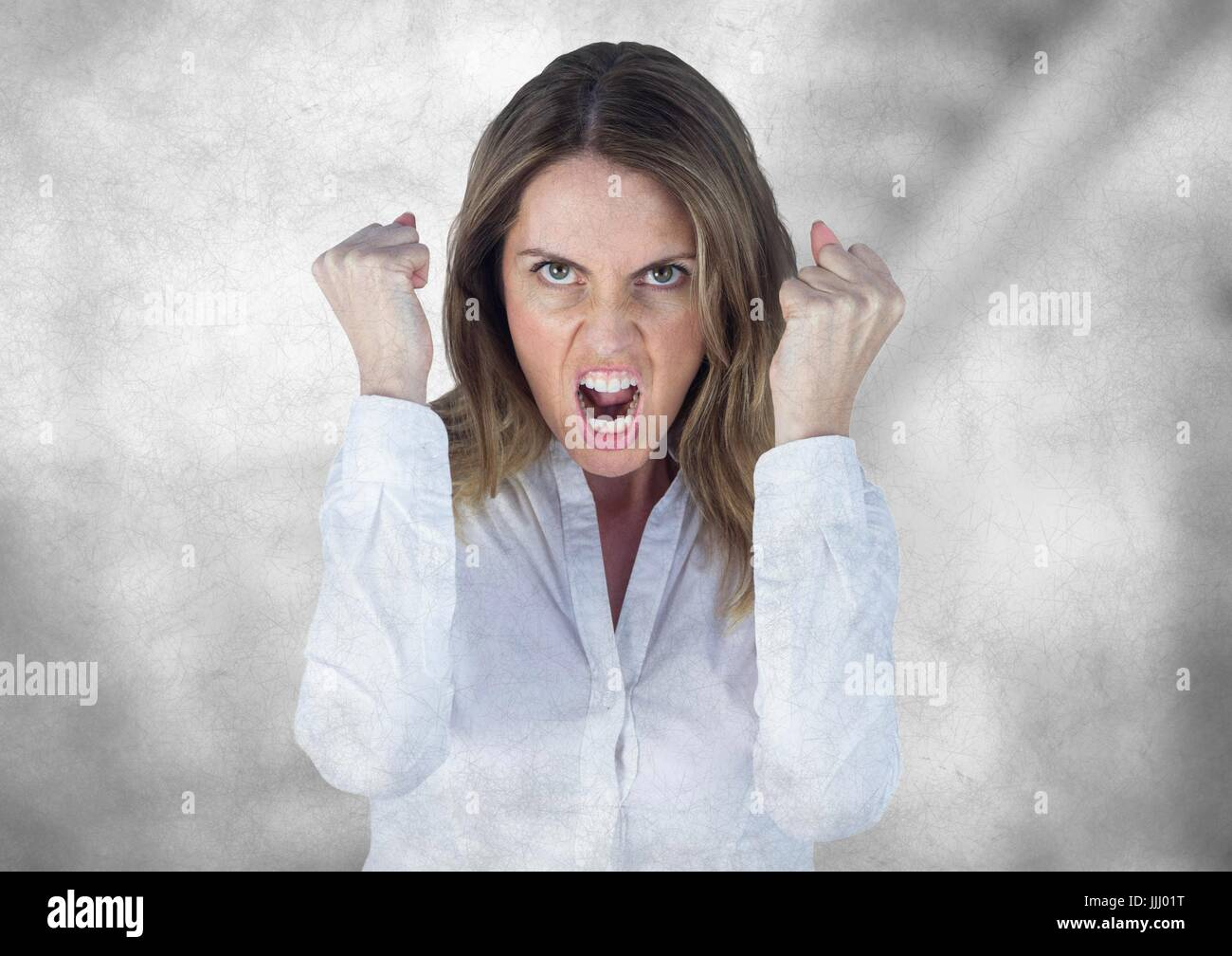 Angry business woman against blurry grey stairs with grunge overlay - Stock Image