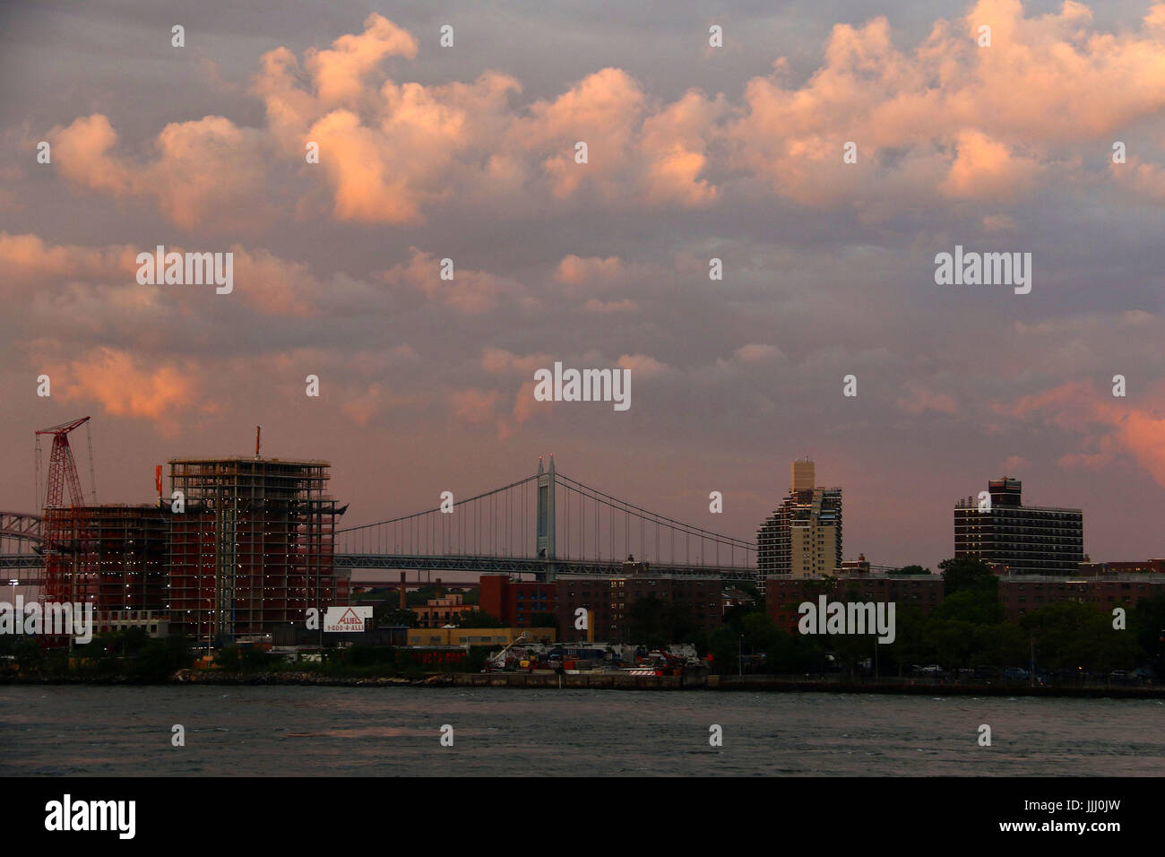Twilight over Triborough Bridge and East River with clouds - Stock Image