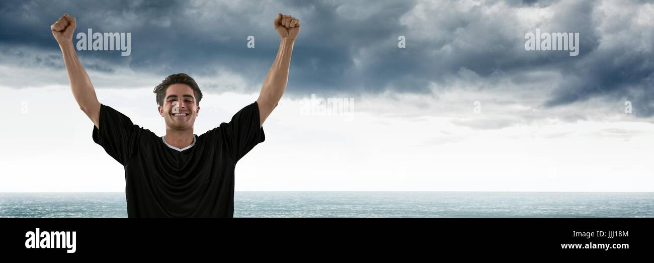 Man in jersey celebrating against grey clouds and water - Stock Image