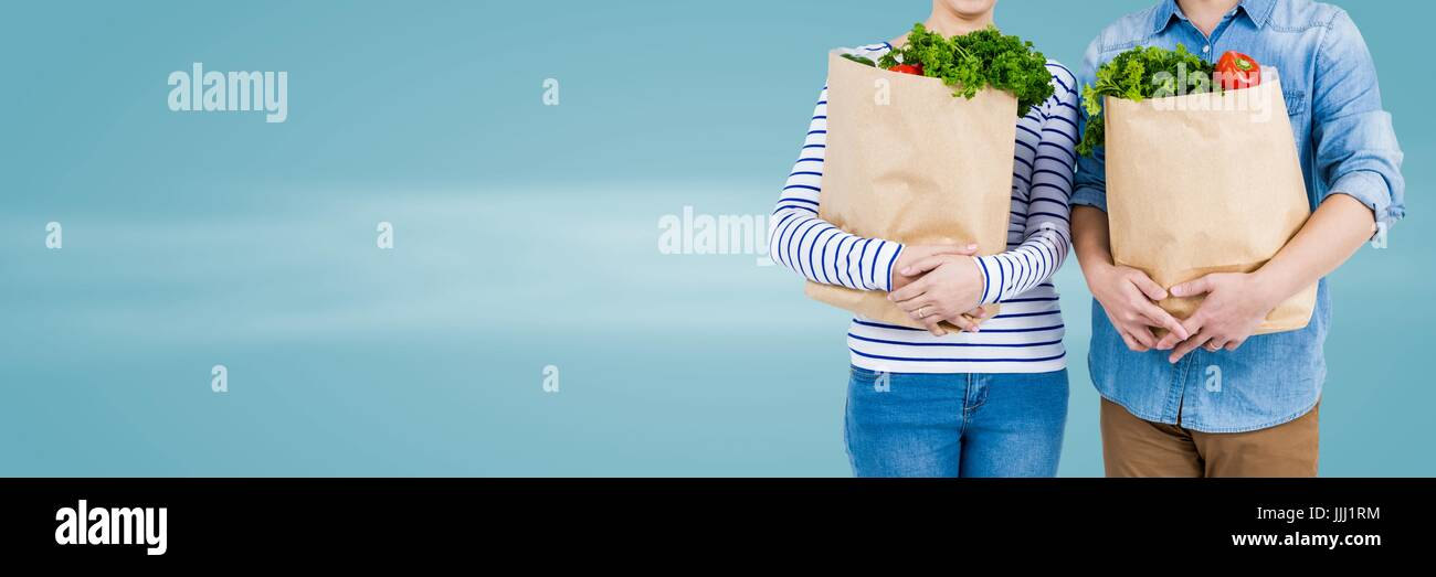 Couple mid sections with grocery bags against blurry blue background and copy space - Stock Image