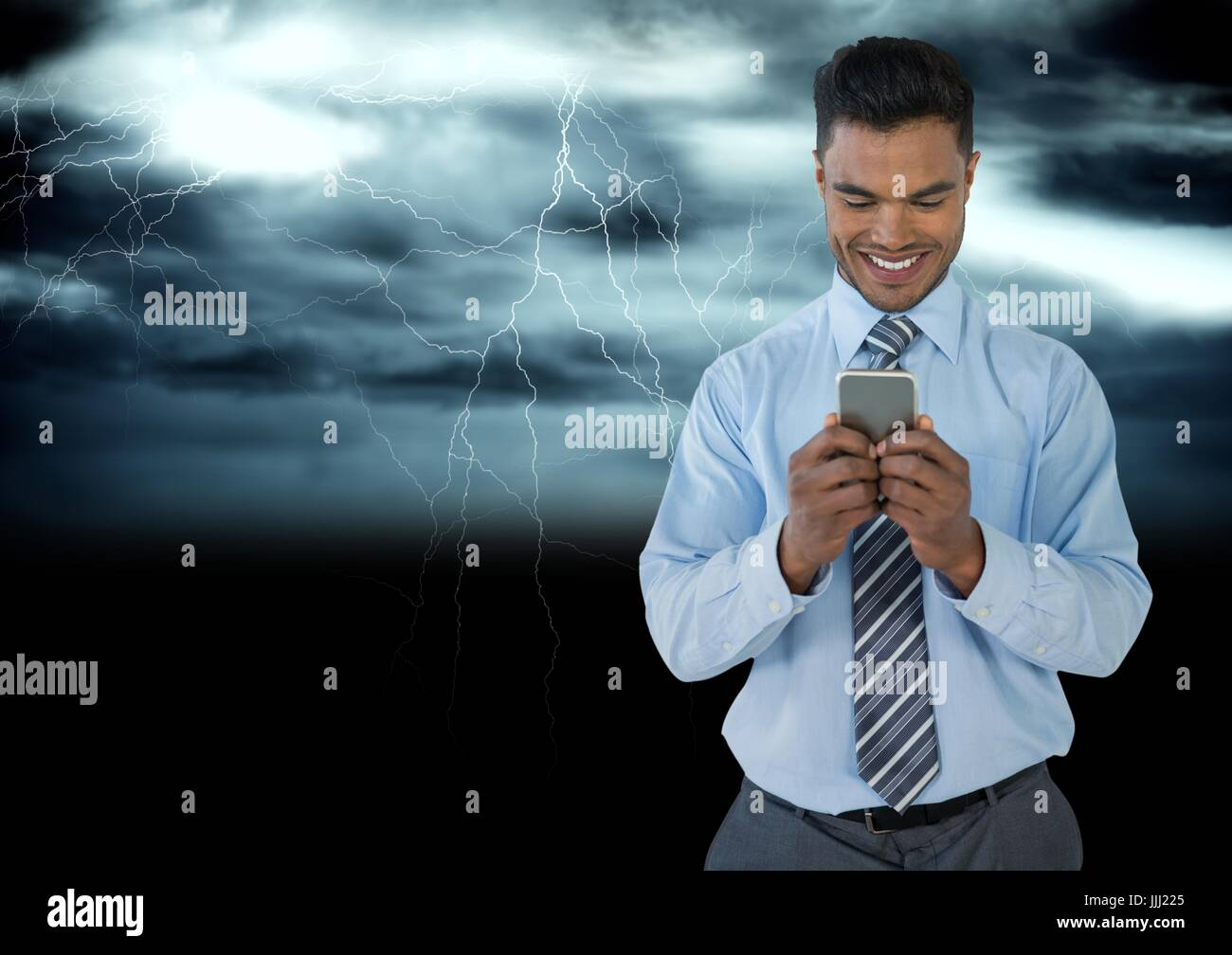Smiling man texting in darkness with lightenings - Stock Image