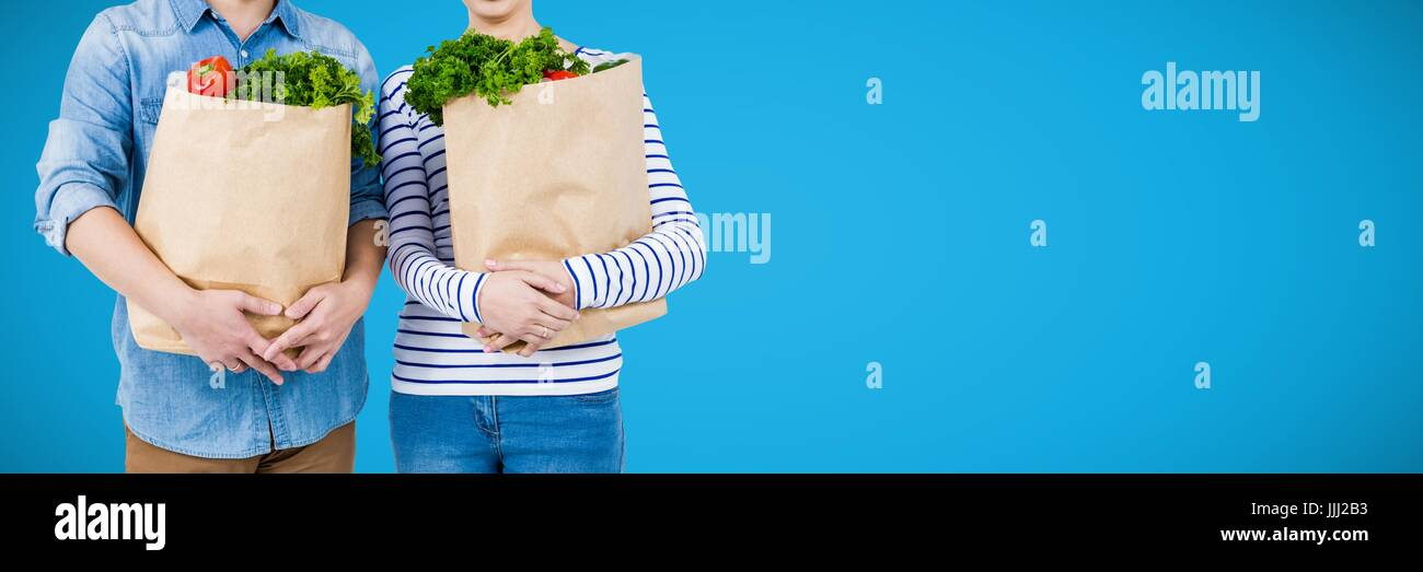 Shoppers mid sections with grocery bags against blue background and copy space - Stock Image