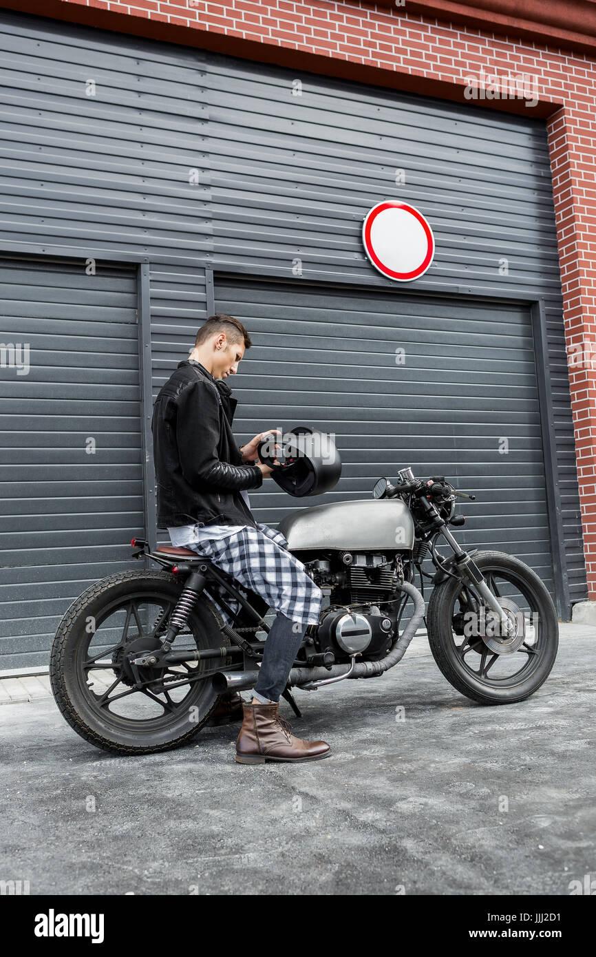 Handsome Rider Guy Put On Black Biker Helmet While Sit Classic Style Cafe Racer Motorcycle Near Industrial Gates Bike Custom Made In Vintage Garag