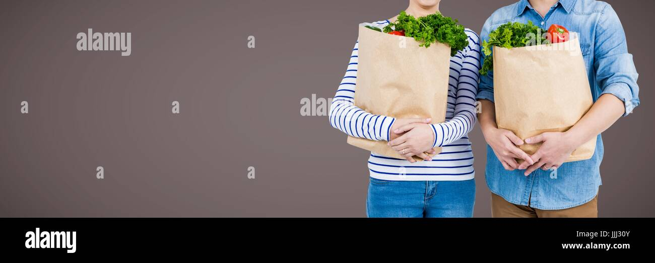 Couples mid sections with grocery bags against brown background 3d - Stock Image