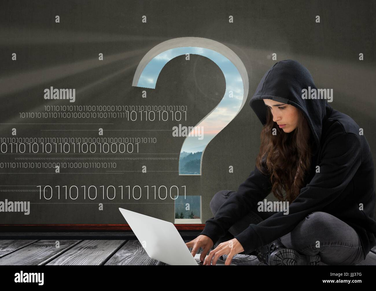 Woman hacker seated and working on a laptop with a grey background with a 3D question mark - Stock Image