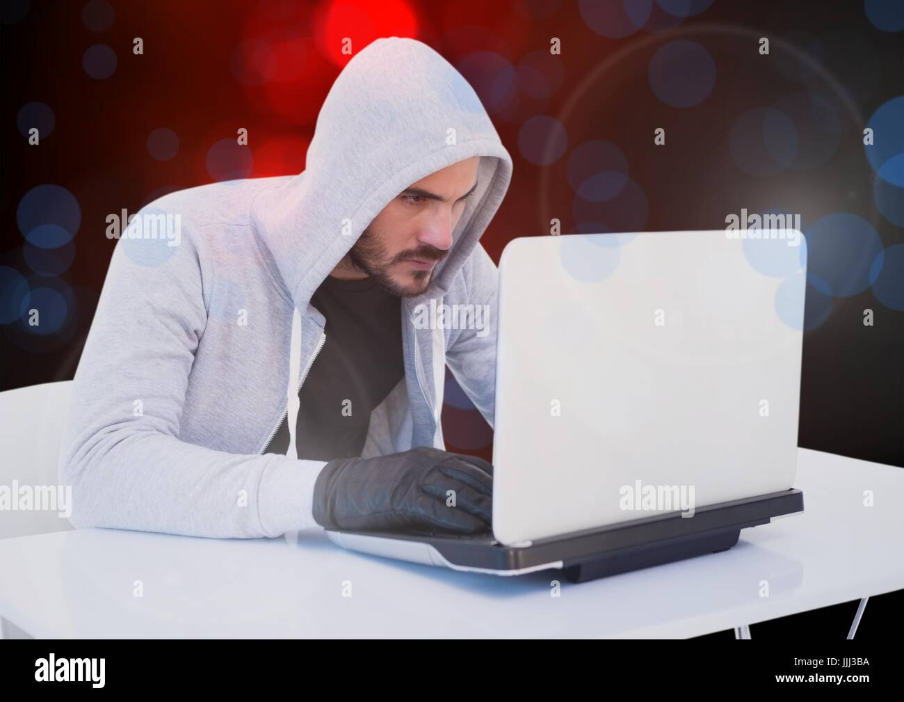 Hacker working on laptop with a digital background - Stock Image