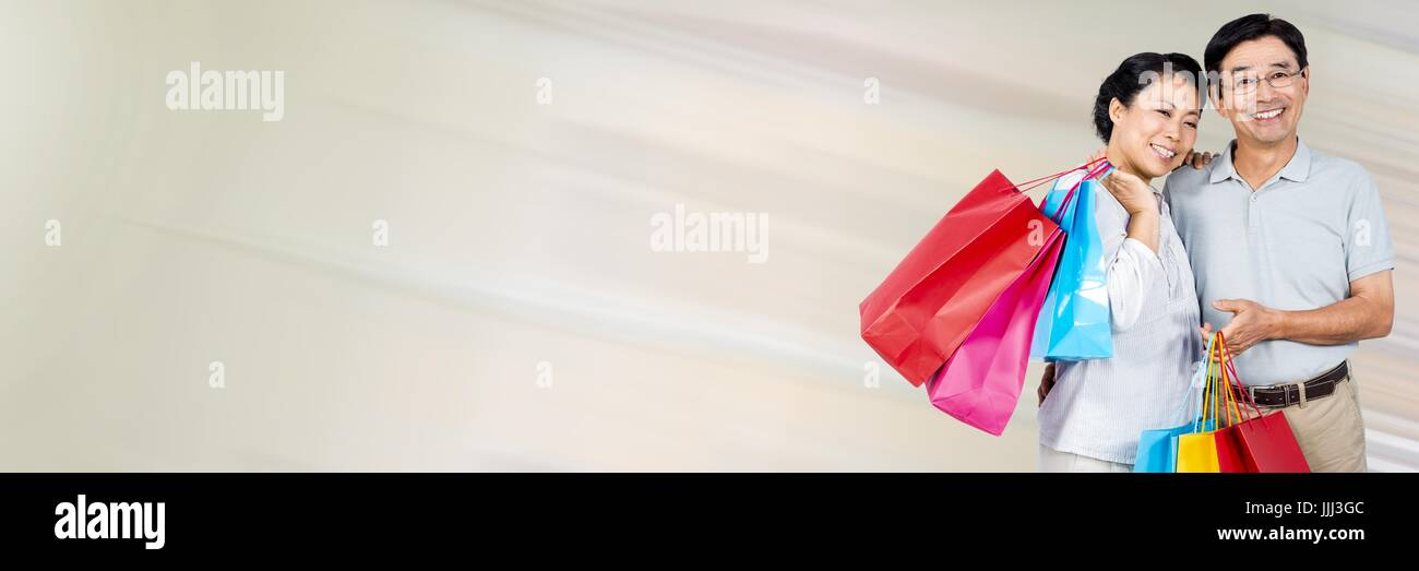Couple with shopping bags against cream motion blur and blank space - Stock Image