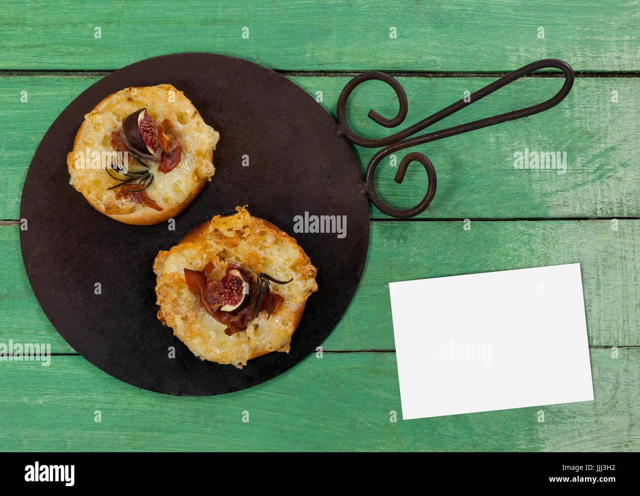 Bussiness card on green wooden desk with food and copy space - Stock Image