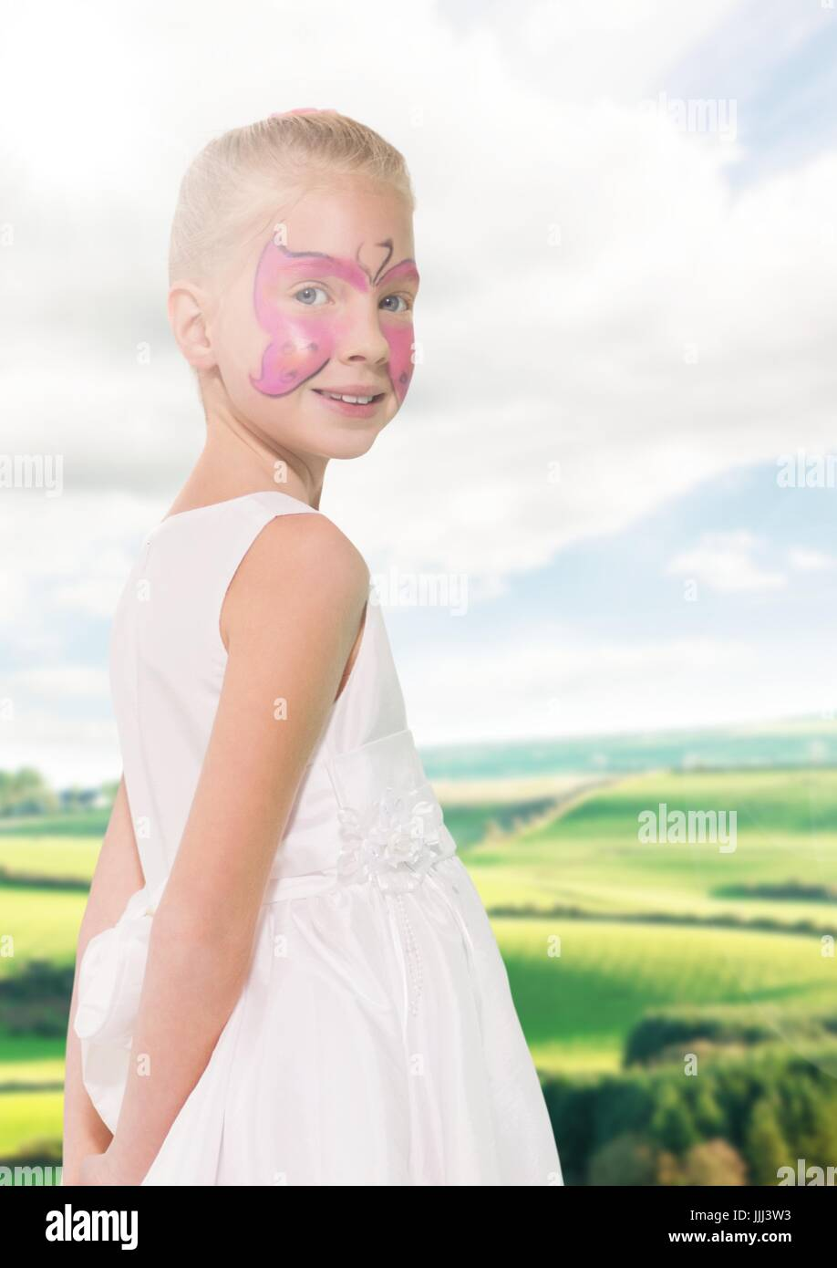 Girl in pink facepaint against fields with flare - Stock Image