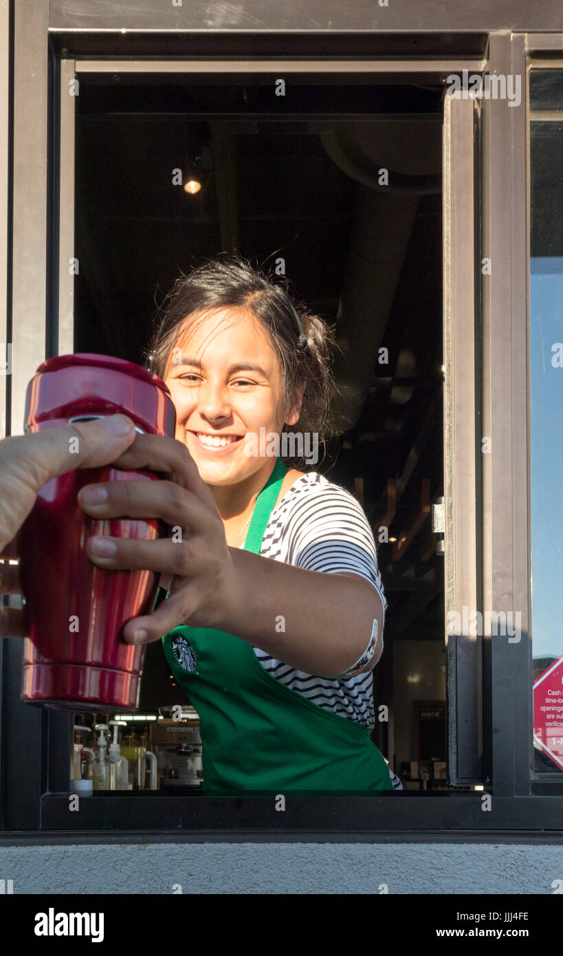 server at Starbucks Drive Thru window taking or receiving coffee travel mug - Stock Image