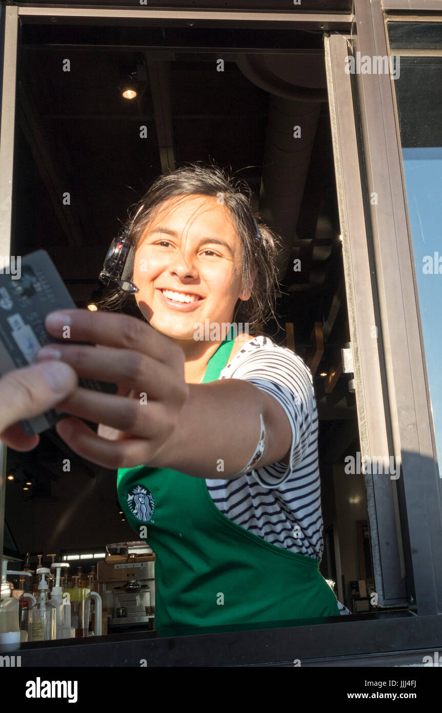 server at Starbucks Drive Thru window taking or receiving payment with credit card - Stock Image