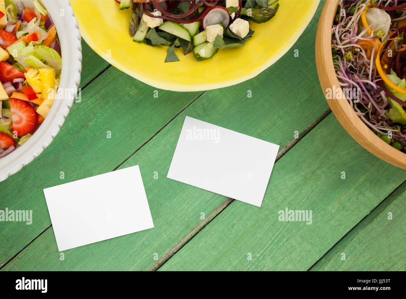 Bussiness cards on green wooden desk with food 3d - Stock Image